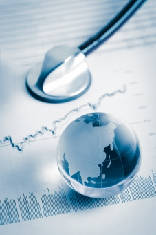 Glass globe and stethoscope on stock chart
